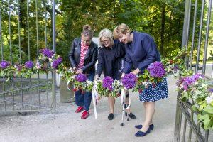 trzy kobiety przecinają kwiatową wstęgę zawieszoną na bramie